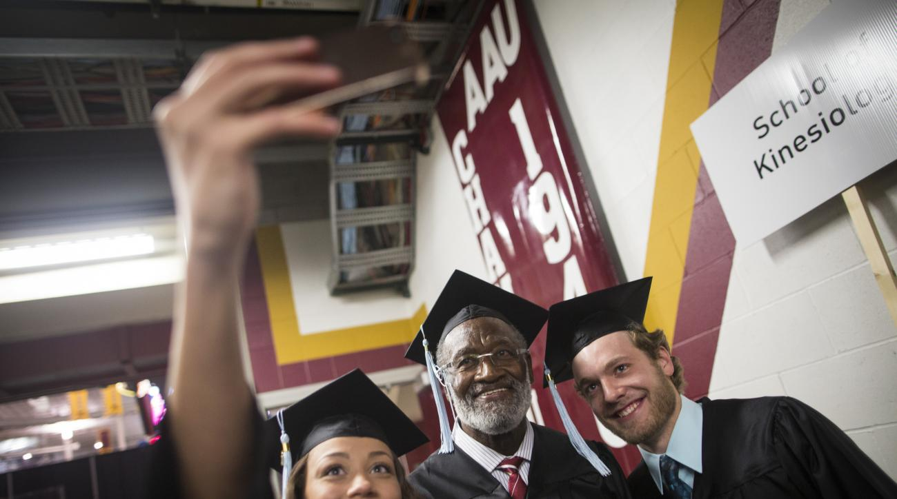 Desiree McGinley, left, and Andrew Otis, right, take a selfie with former Gophers great and Pro Football Hall of Famer Bobby Bell as they line up for the procession before graduating college, Thursday, May 14, 2015, at Mariucci Arena at the University of