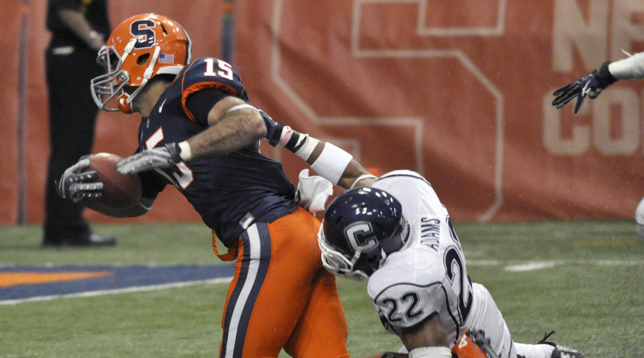 Syracuse's Alec Lemon is dragged down from behind by Connecticut's Andrew Adams during the third quarter of an NCAA college football game in Syracuse, N.Y., Friday, Oct. 19, 2012. Syracuse won 40-10. (AP Photo/Kevin Rivoli)