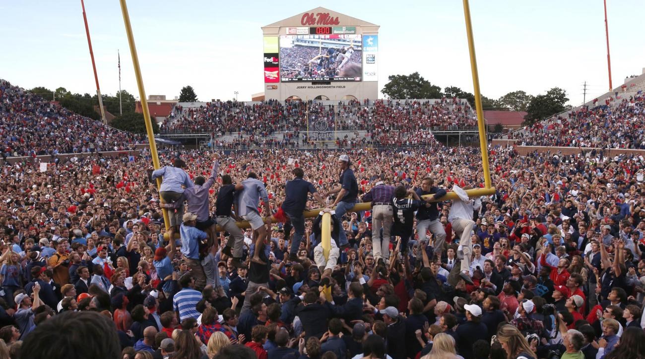 FILE - In this Oct. 4, 2014, file photo, Mississippi fans gather on the field, while a few climb onto a goal post, after Mississippi defeated Alabama 23-17 in an NCAA college football game in Oxford, Miss. The Southeastern Conference has been fining teams