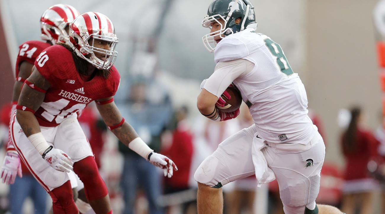 Michigan State tight end Josiah Price (82) scores against Indiana safety Antonio Allen (40) during the first half of an NCAA college football game in Bloomington, Ind., Saturday, Oct. 18, 2014. (AP Photo/Sam Riche)