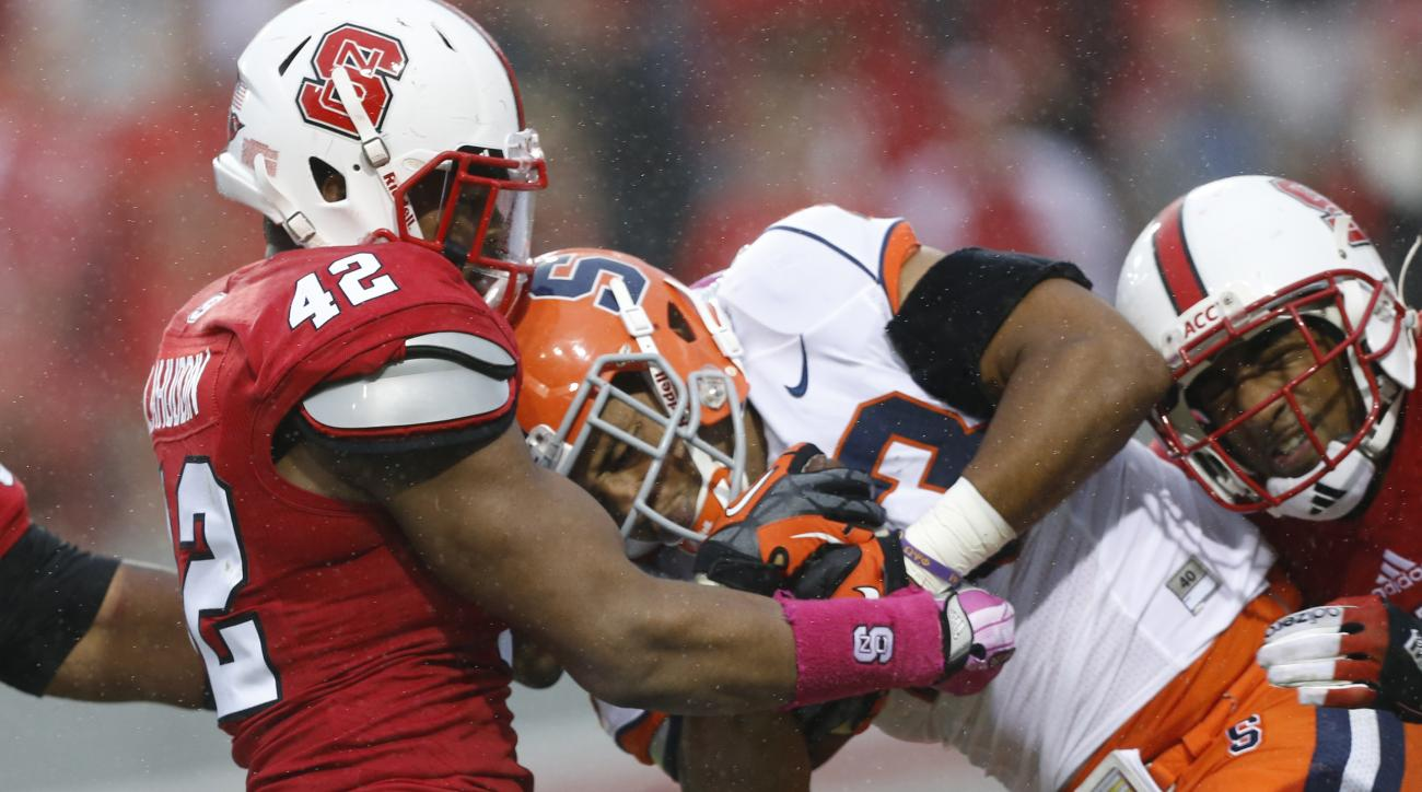 In this photo taken Oct. 12, 2013, North Carolina State's M.J. Salahuddin (42) stops Syracuse's Prince-Tyson Gulley (23) during an NCAA college football game at Carter-Finley Stadium in Raleigh, N.C. Salahuddin was perfectly positioned to seize a leading