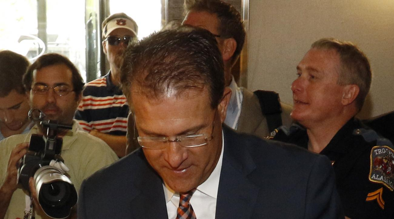 Auburn coach Gus Malzahn signs an autograph for a fan at the Southeastern Conference NCAA college football media days, Monday, July 13, 2015, in Hoover, Ala. (AP Photo/Butch Dill)