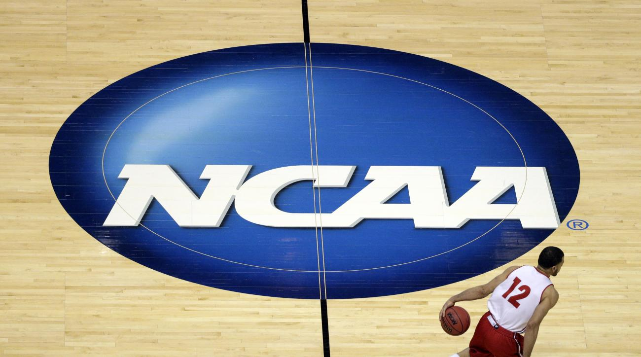 FILE - In this March 26, 2014, file photo, Wisconsin's Traevon Jackson dribbles past the NCAA logo during practice at the NCAA men's college basketball tournament in Anaheim, Calif. A federal judge ruled that the NCAA can't stop players from selling the r