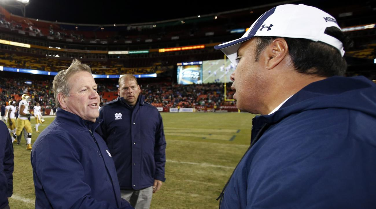 Notre Dame coach Brian Kelly, left, greets Navy coach Ken Niumatalolo after an NCAA college football game, Saturday, Nov. 1, 2014, in Landover, Md. Notre Dame won 49-39. (AP Photo/Alex Brandon)