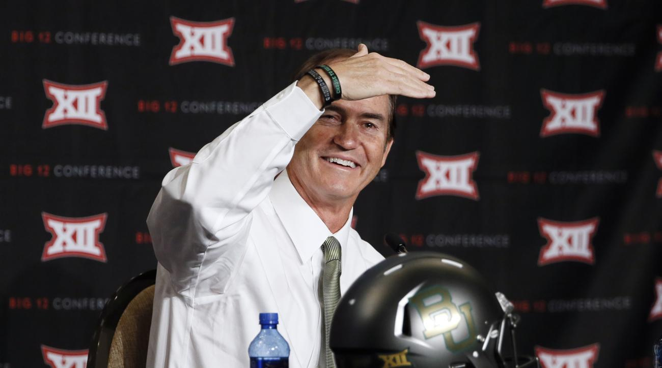 FILE - In this July 21, 2015, file photo, Baylor head coach Art Briles shields his eyes from the lights as he addresses attendees at the Big 12 Conference Football Media Days in Dallas. The quarterback is usually the face of a football team. During confer