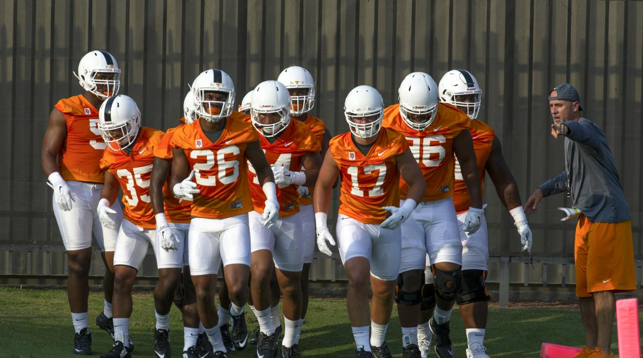 Tennessee defensive backs coach Willie Martinez directs players including MaLeik Gatewood (35), Stephen Griffin (26), and Dillon Bates (17) during the team's first NCAA college football practice of the season Tuesday, Aug. 4, 2015, in Knoxville, Tenn. (Je