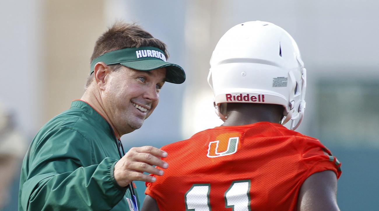 Miami head coach Al Golden speaks with wide receiver Rashawn Scott during an NCAA college football practice, Friday, Aug. 7, 2015, in Coral Gables, Fla. The team is not bothered by a national perception that they will struggle this season. (AP Photo/Joe S