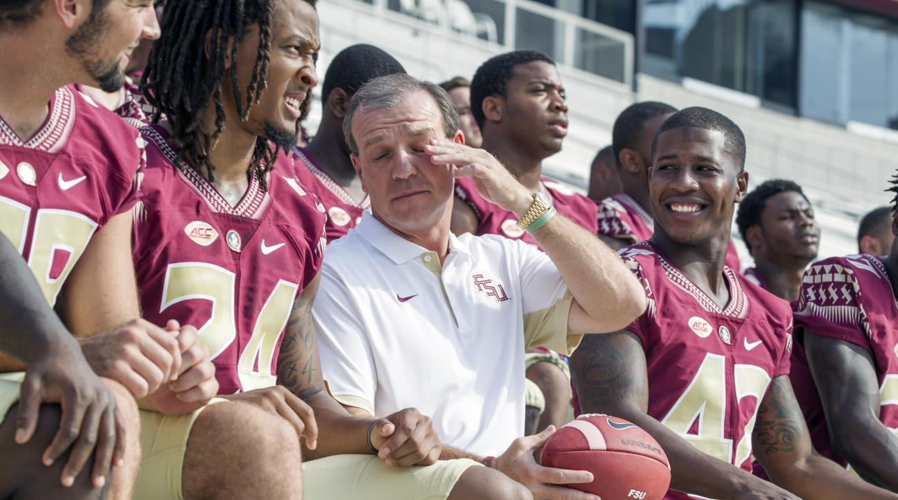 Florida State head coach Jimbo Fisher, center, shields his eyes while waiting for the team photo during NCAA college football media day in Tallahassee, Fla., Sunday, Aug. 9, 2015. (AP Photo/Mark Wallheiser)