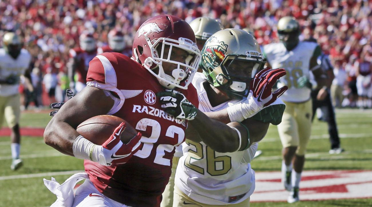 FILE - in this Oct. 25, 2014, file photo, Arkansas running back Jonathan Williams (32) pushes away UAB cornerback Rolan Milligan (26) during an NCAA college football game in Fayetteville, Ark. Exactly how much the Razorbacks can improve on last season's s
