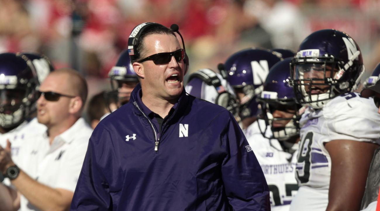 FILE - In this Oct. 12, 2013 file photo, Northwestern coach Pat Fitzgerald directs his team during the first half of an NCAA college football game in Madison, Wis. On the outside, it is the same frenetic Fitzgerald. On a typically warm August afternoon, h