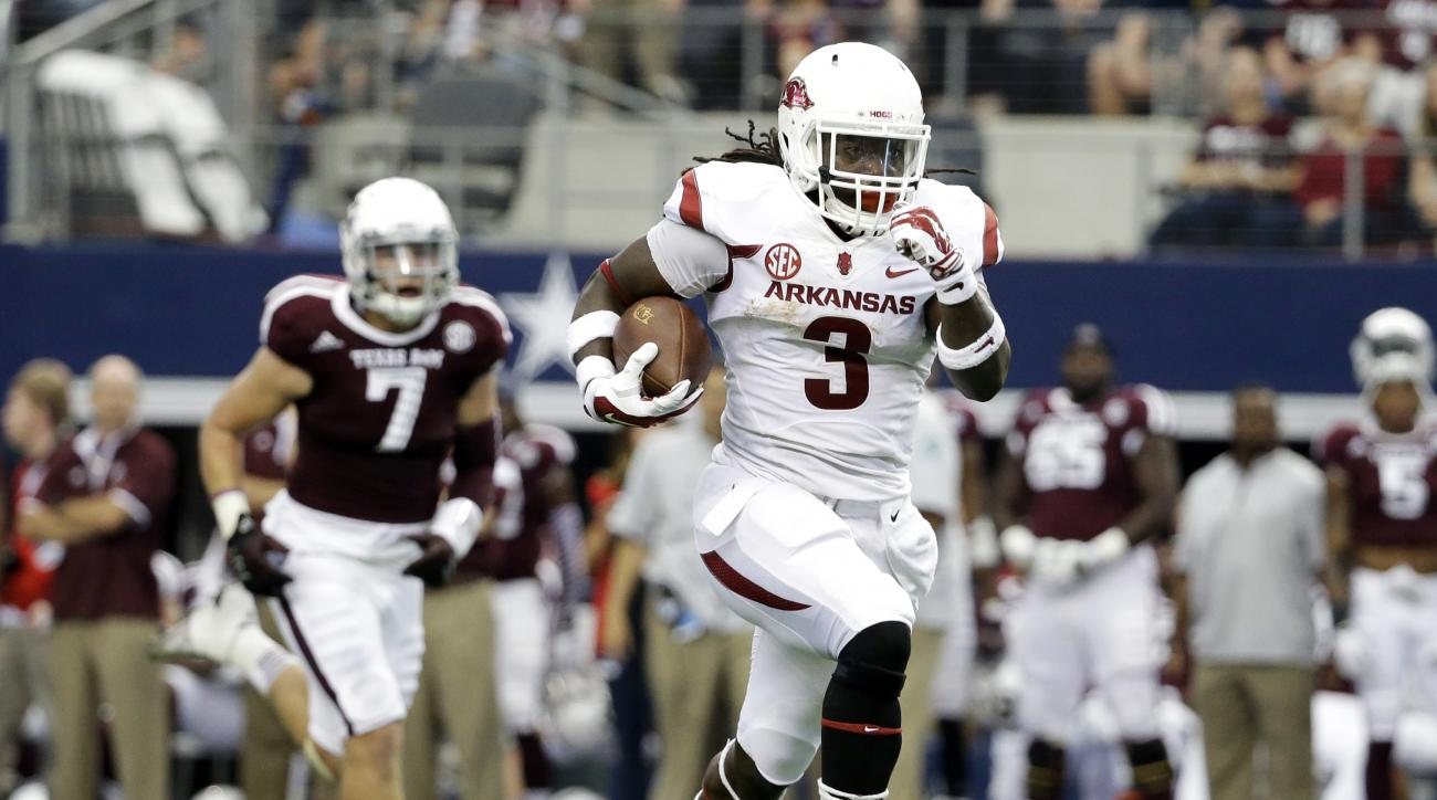 FILE - In this Sept. 27, 2014, file photo, Arkansas running back Alex Collins (3) sprints past Texas A&M linebacker Jordan Mastrogiovanni (7) for a long run on his way to the end zone for a touchdown in the first half of an NCAA college football game in A