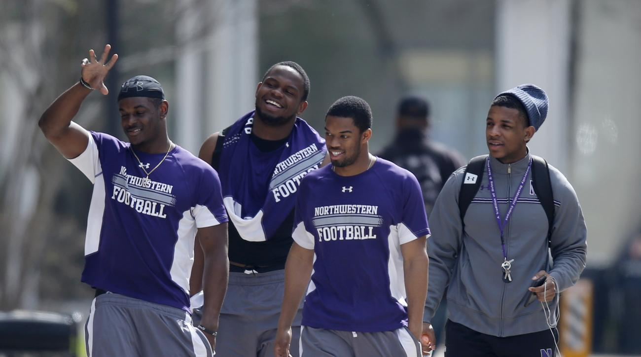 FILE - In this April 25, 2014, file photo, unidentified Northwestern football players walk between their locker room and McGaw Hall, where voting is taking place on the student athlete union question, in Evanston, Ill. The National Labor Relations Board h