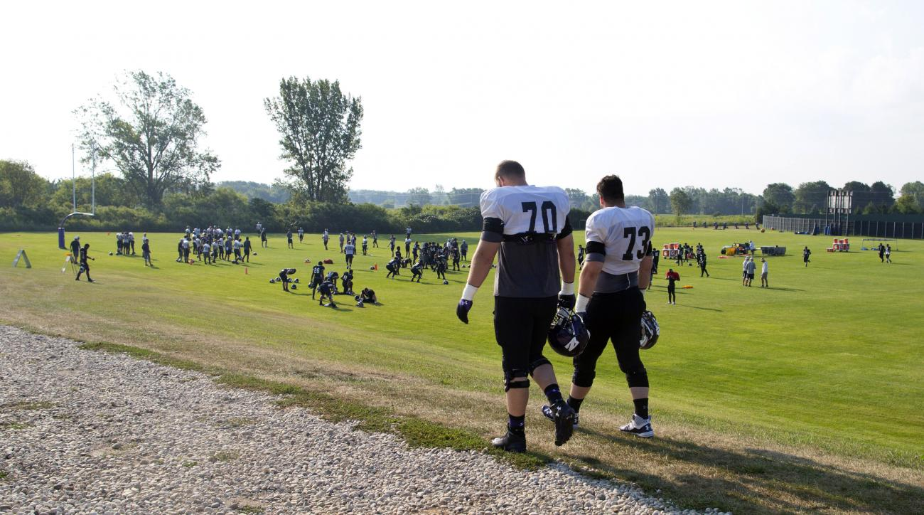 Northwestern football players Shane Mertz (70) and Adam DePietro (73) walk to practice at the University of Wisconsin-Parkside campus on Monday, Aug. 17, 2015, in Kenosha, Wi. The National Labor Relations Board on Monday overturned a historic ruling that