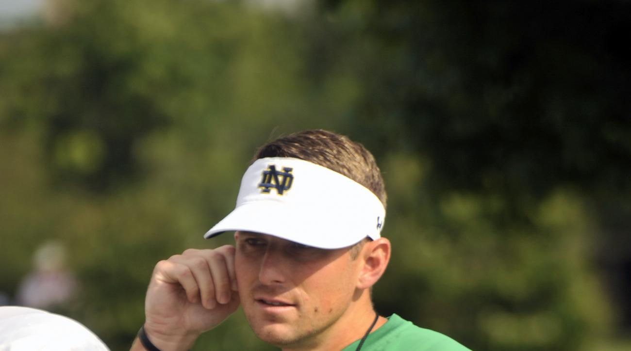 In this Saturday, Aug. 15, 2015, photo, Notre Dame offensive coordinator Mike Sanford walks onto the practice field during an  NCAA college football practice in South Bend, Ind. Sanford is Notre Dame's new offensive coordinator but what exactly does that