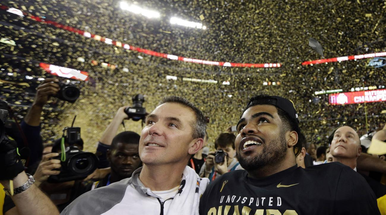 FILE - In this Jan. 12, 2015, file photo, Ohio State head coach Urban Meyer, left, and Ezekiel Elliott celebrate after they defeated Oregon 42-20 in the NCAA college football playoff championship game in Arlington, Texas. Ezekiel Elliott and the Ohio Stat