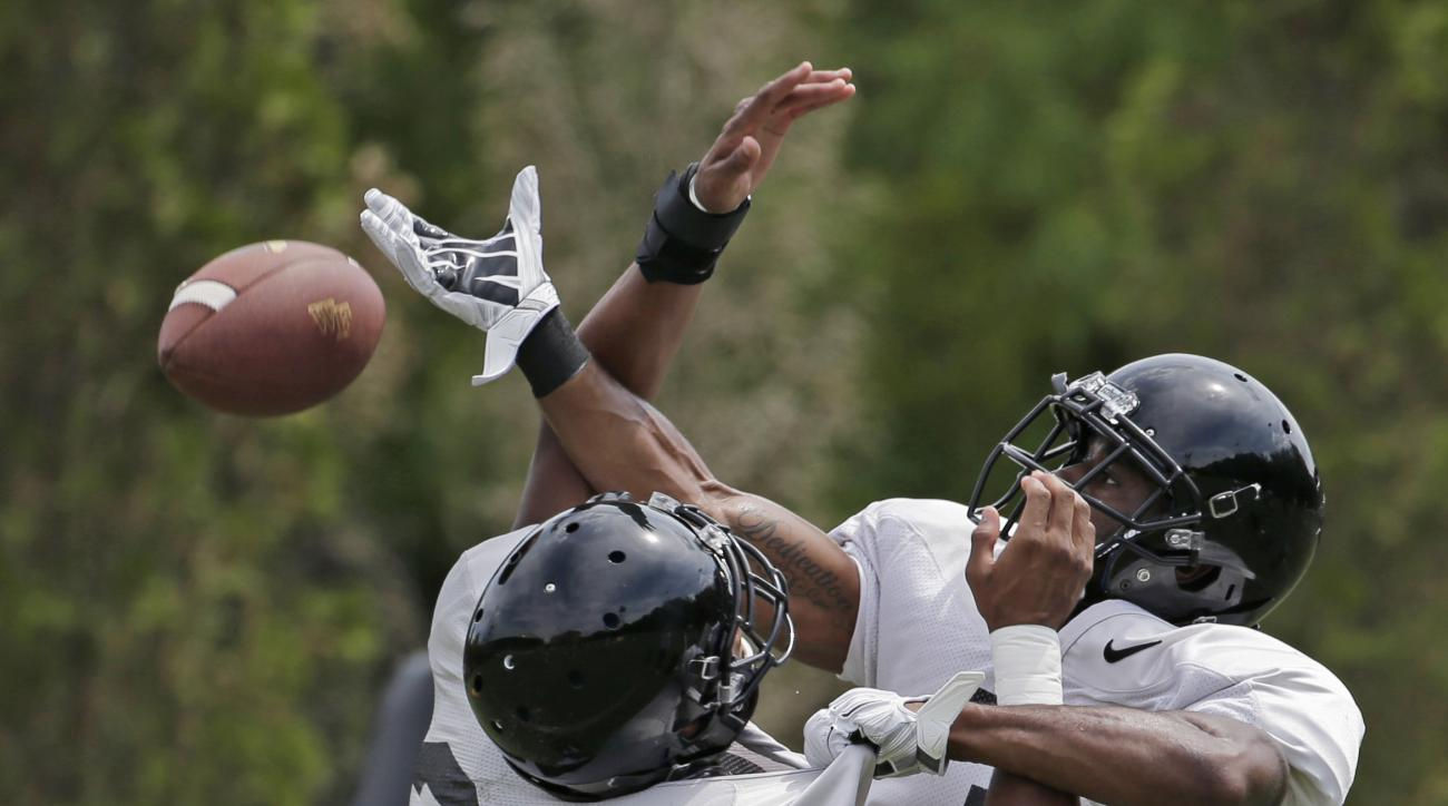 In this Thursday, Aug. 13, 2015, photo, Wake Forest's Devin Gaulden, right, and Brad Watson, left, run a drill during NCAA college football practice in Winston-Salem, N.C. (AP Photo/Chuck Burton)