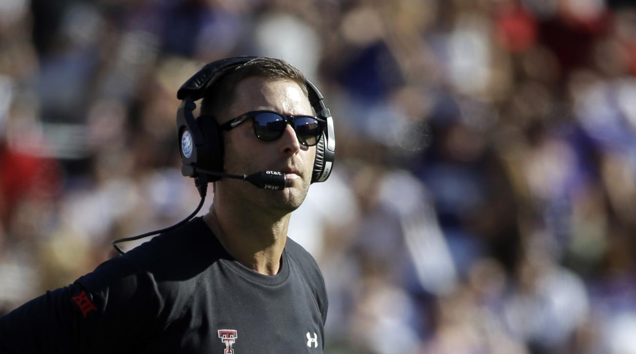 "FILE - In this Oct. 25, 2014, file photo, Texas Tech head coach Kliff Kingsbury watches play in the first half of an NCAA college football game against TCU in Fort Worth, Texas. Kingsbury calls his options at quarterback this season a ""luxury."" Sophomore"