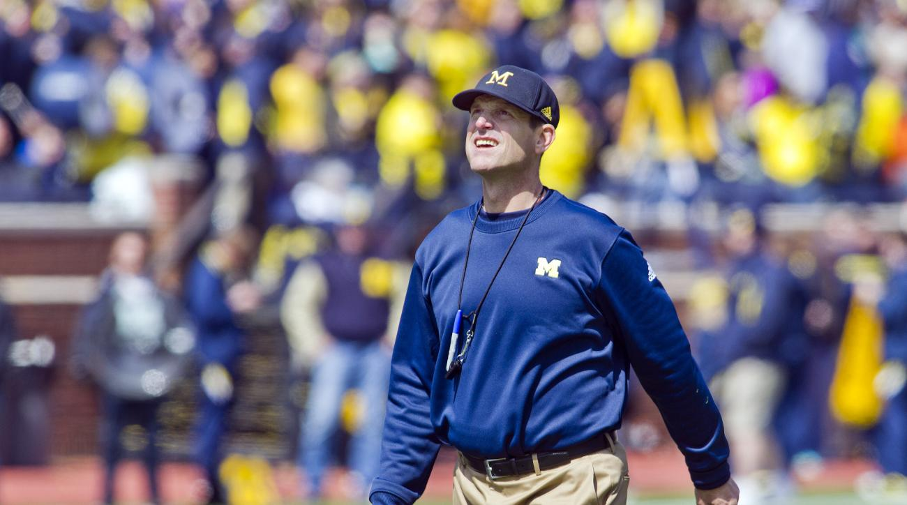 FILE - In this April 4, 2015, file photo, Michigan head coach Jim Harbaugh walks the field between downs during the NCAA college football team's spring game in Ann Arbor, Mich. Now Harbaugh will finally begin coaching the Wolverines in some actual games _