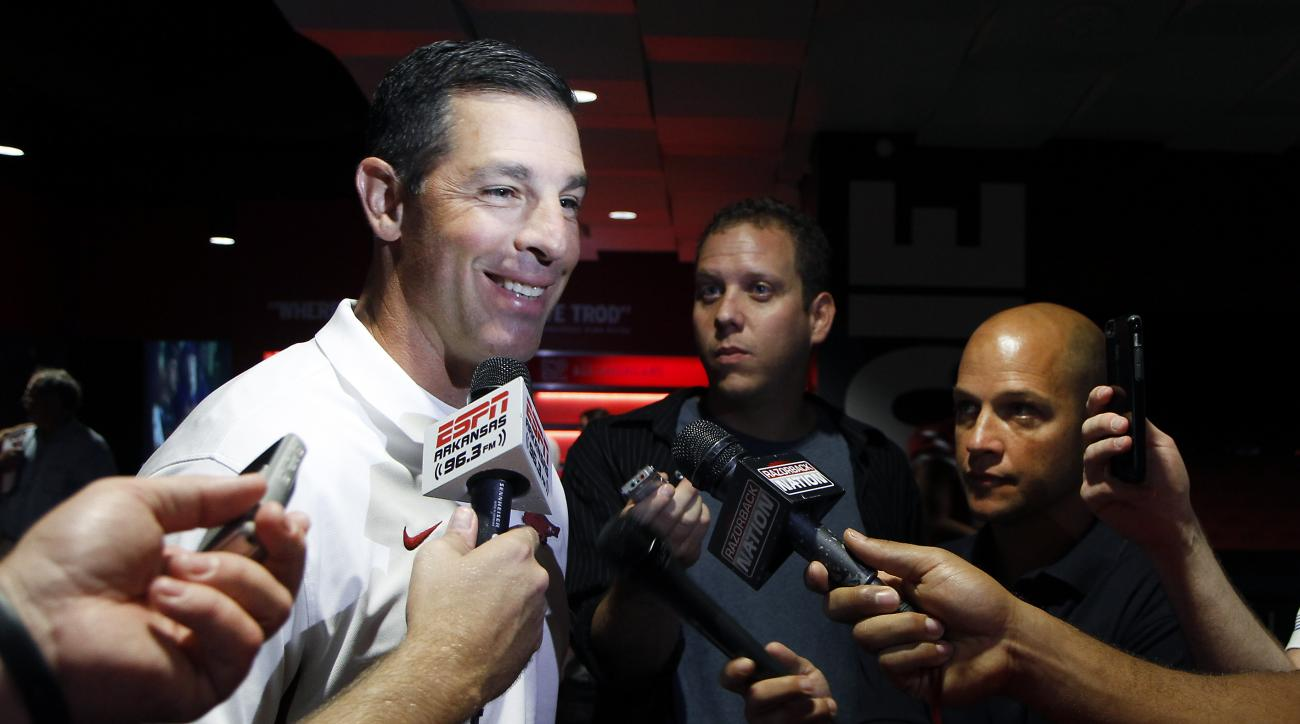 In this Aug. 9, 2015, photo, Arkansas offensive coordinator Dan Enos speaks to members of the media during an NCAA college football media day event in Fayetteville, Ark. Enos left his job as head coach at Central Michigan after last season to take over as