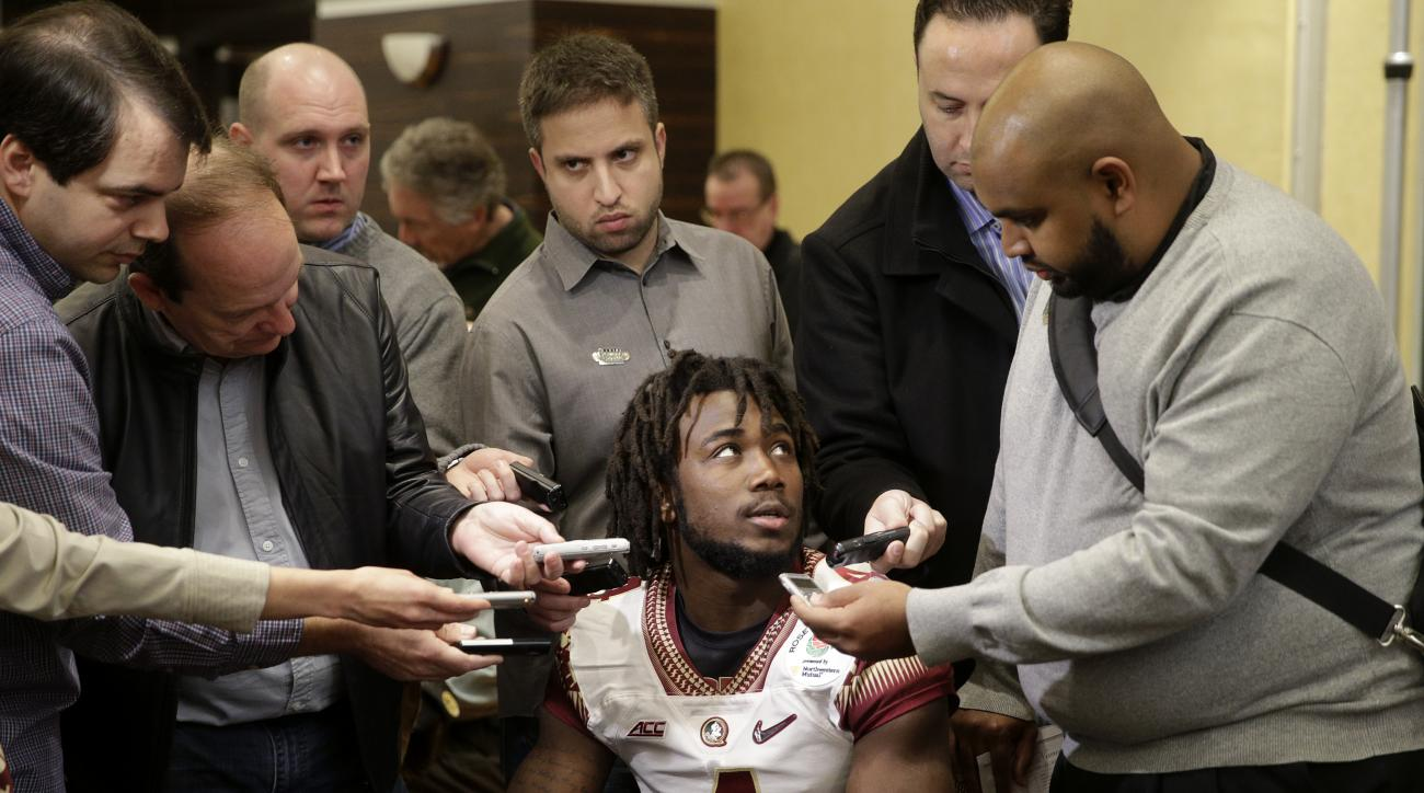 FILE - In this Dec. 29, 2014, file photo, Florida State running back Dalvin Cook, center, is surrounded by reporters during the team's media day, for the Rose Bawl,  in Los Angeles. The trial for suspended Florida State running back Dalvin Cook on charges