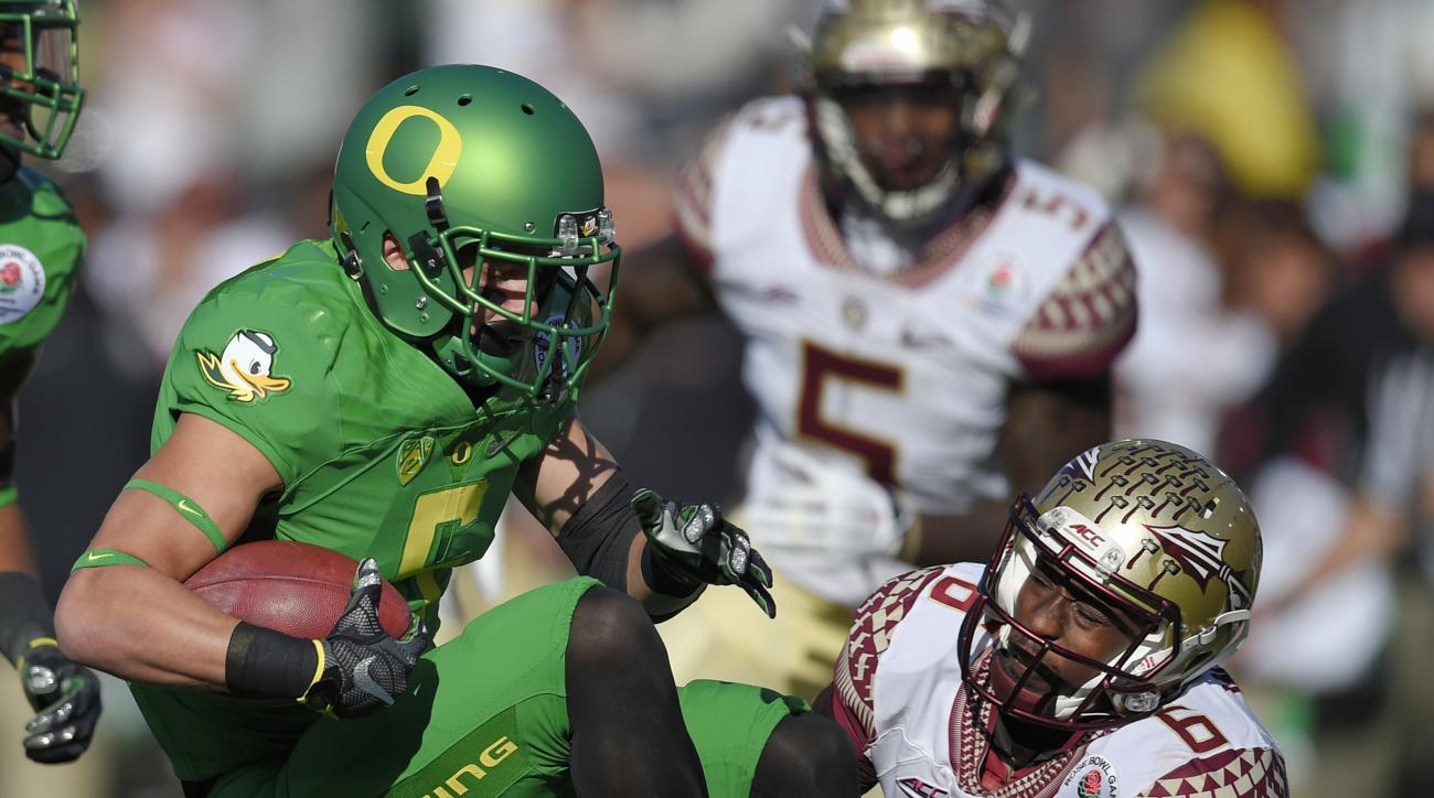 FILE - In this Jan. 1, 2015, file photo, Oregon wide receiver Devon Allen, left, is tackled by Florida State linebacker Reggie Northrup during the first half of the Rose Bowl NCAA college football playoff semifinal in Pasadena, Calif.   Allen tore his ACL