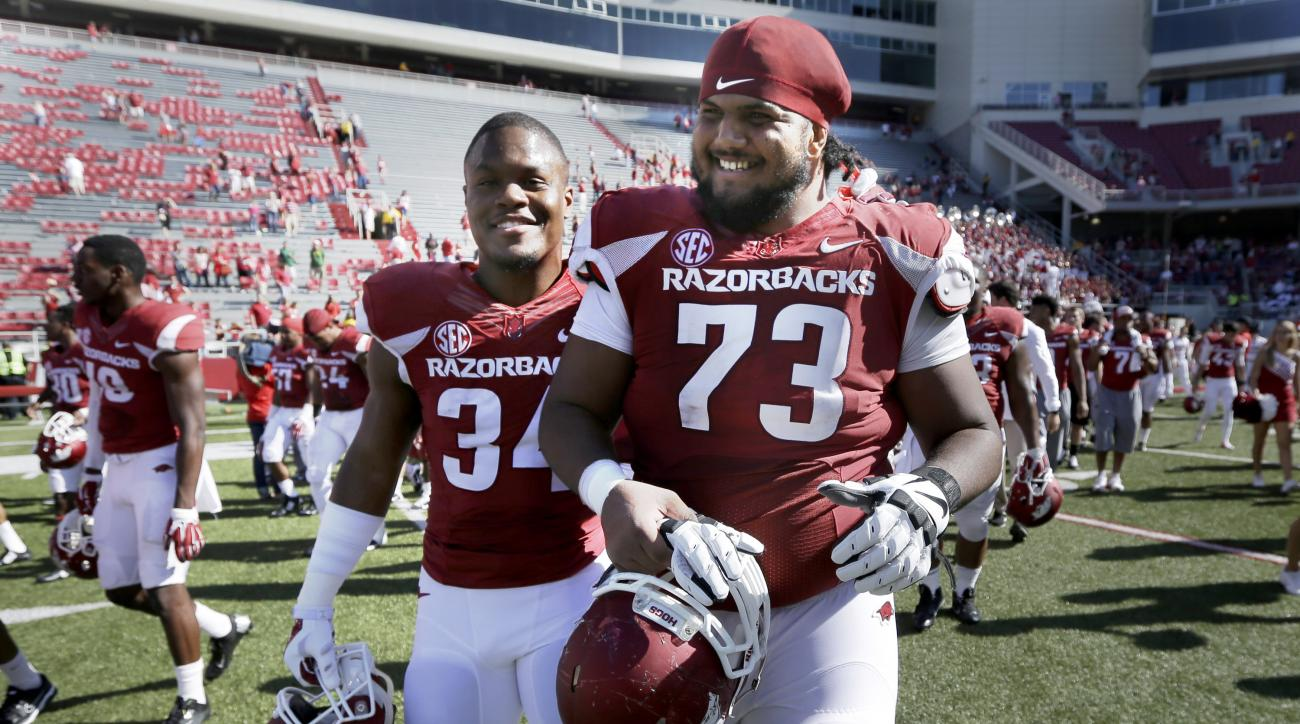 FILE - In this Oct. 25, 2014, file photo, Arkansas offensive tackle Sebastian Tretola (73) and linebacker Braylon Mitchell (34) walk off the field after an NCAA college football game against UAB in Fayetteville, Ark. Arkansas offensive lineman Sebastian T