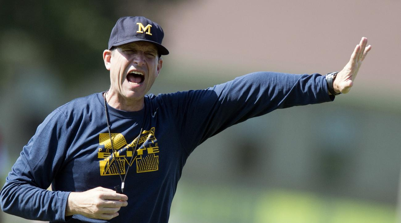 Michigan football coach Jim Harbaugh yells during the Coach Jim Harbaugh's Elite Summer Football Camp, Friday, June 5, 2015, at Prattville High School in Prattville, Ala. Harbaugh will have to improve the Wolverines by one game over last season to get the