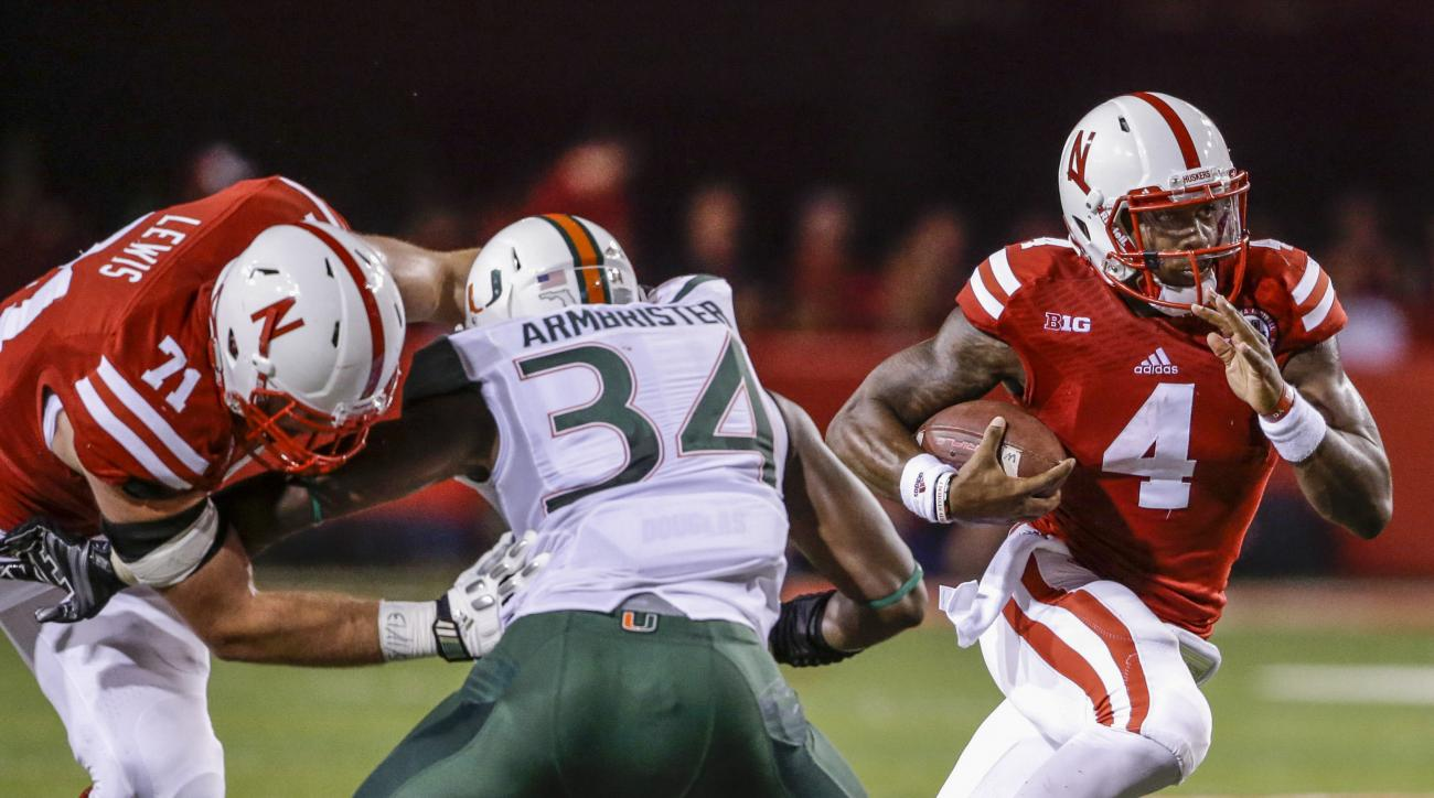 FILE - In this Sept. 20, 2014, file photo, Nebraska quarterback Tommy Armstrong Jr. (4) runs through a gap as offensive lineman Alex Lewis (71) blocks Miami linebacker Thurston Armbrister (34) in the second half of an NCAA college football game in Lincoln