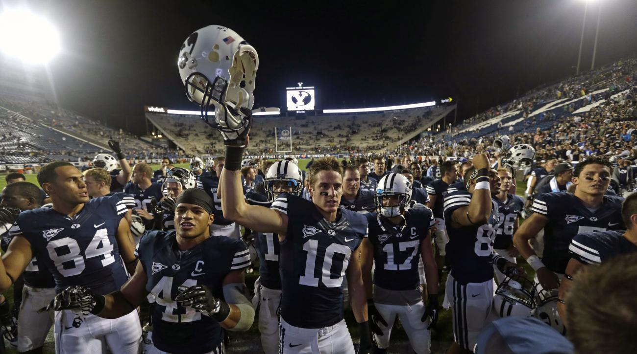 FILE - This Sept. 7, 2013, file photo, shows Brigham Young's Devin Mahina (84), Uani Unga (41) and Mitch Mathews (10) celebrating with other players following their NCAA college football game against Texas, in Provo, Utah. BYU has visions of mismatches ac