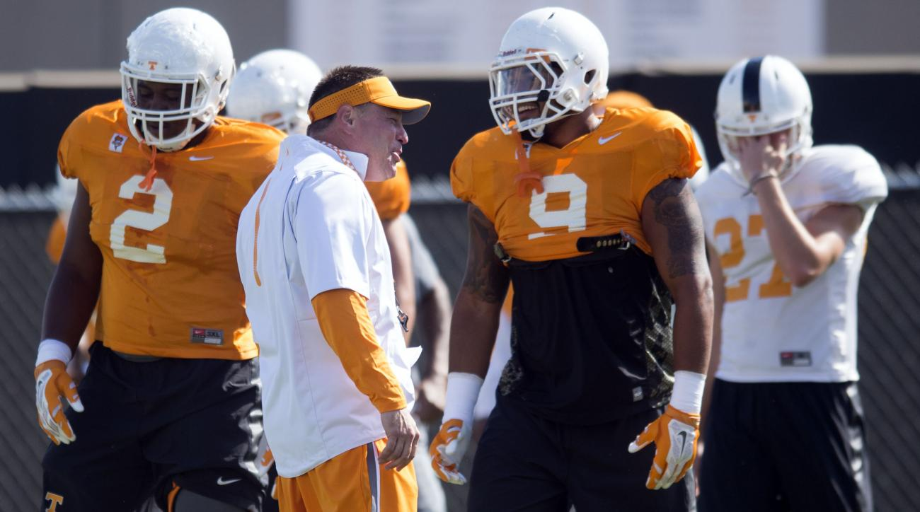 In this Aug. 26, 2015, photo, Tennessee coach Butch Jones talks with players including Tennessee defensive end Derek Barnett (9) during practice in Knoxville, Tenn. Defensive lineman Shy Tuttle is at left. Derek Barnett aned Curt Maggitt make No. 25 Tenne