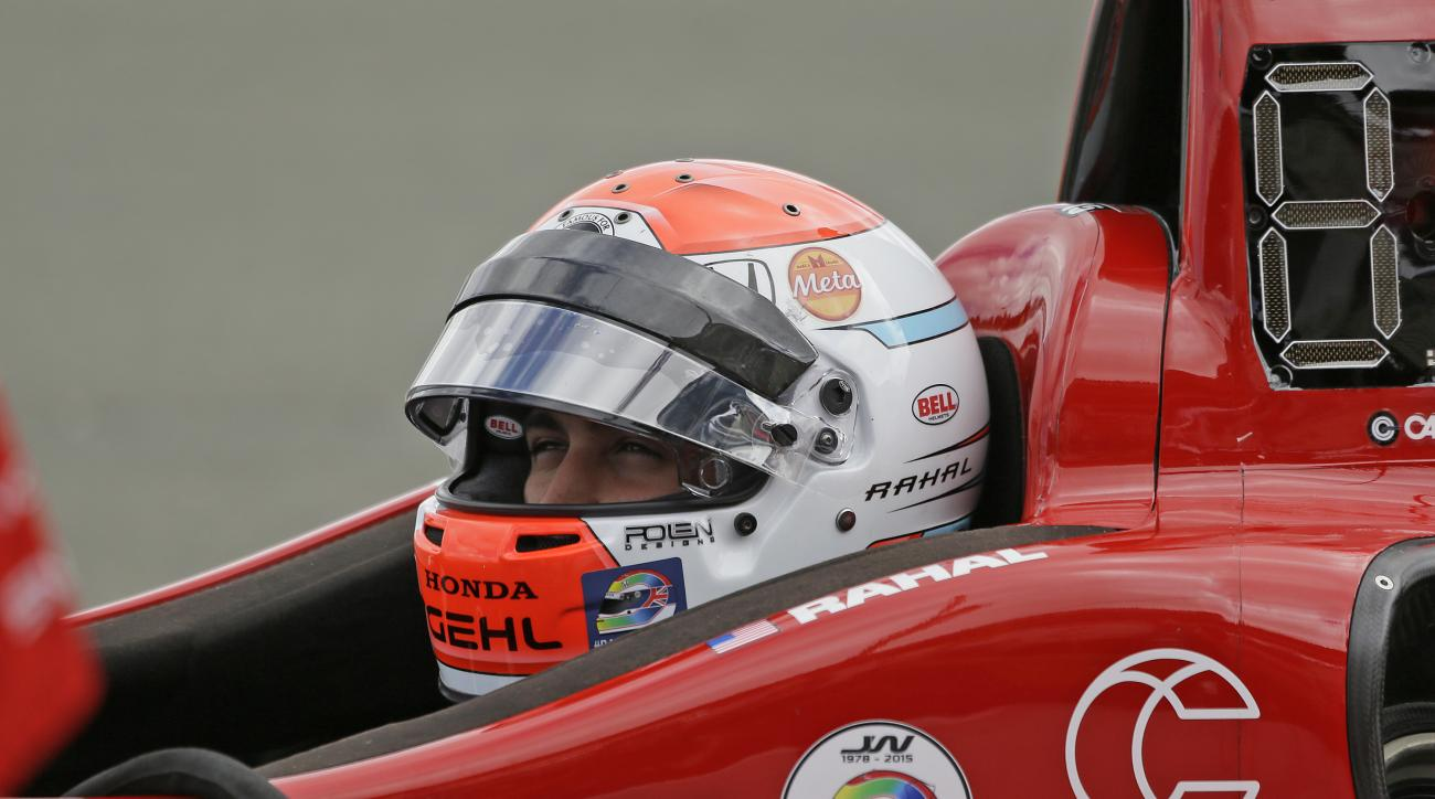 Graham Rahal waits in his car for the start of practice for the IndyCar auto race Saturday, Aug. 29, 2015, in Sonoma, Calif. Stickers on Rahal's car and helmet pay tribute to Justin Wilson, of Great Britain, who died Aug. 24 from injuries sustained at Poc
