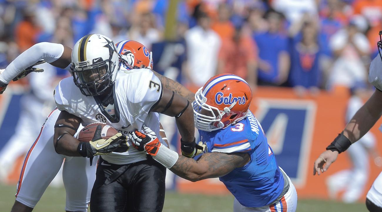 FILE - In this Nov. 9, 2013, file photo, Florida linebacker Antonio Morrison (3) tries to bring him Vanderbilt running back Jerron Seymour (3) during the first half of an NCAA college football game  in Gainesville, Fla. Morrison, who injured his left knee