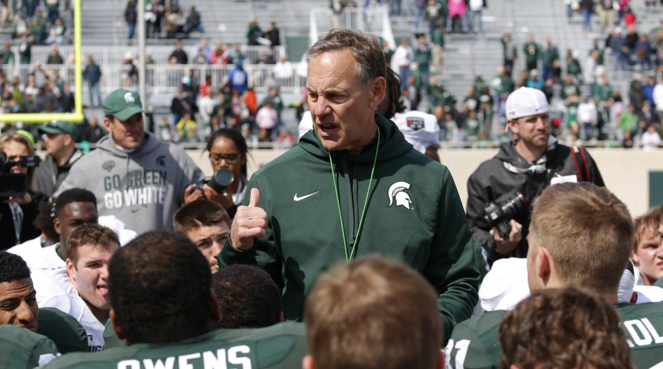 FILE - In this April 25, 2015, file photo, Michigan State coach Mark Dantonio, center, talks to his players following an NCAA college football scrimmage in East Lansing, Mich. Dantonio's toughest job this week might be making sure No. 5 Michigan State is