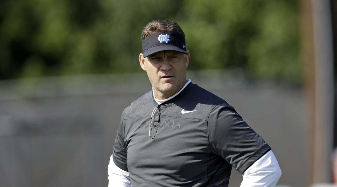 FILE - In this Aug. 3, 2015 file photo, North Carolina defensive coordinator Gene Chizik watches players during the team's first NCAA college football practice of the season in Chapel Hill, N.C. North Carolina has overhauled its defensive coaching staff a