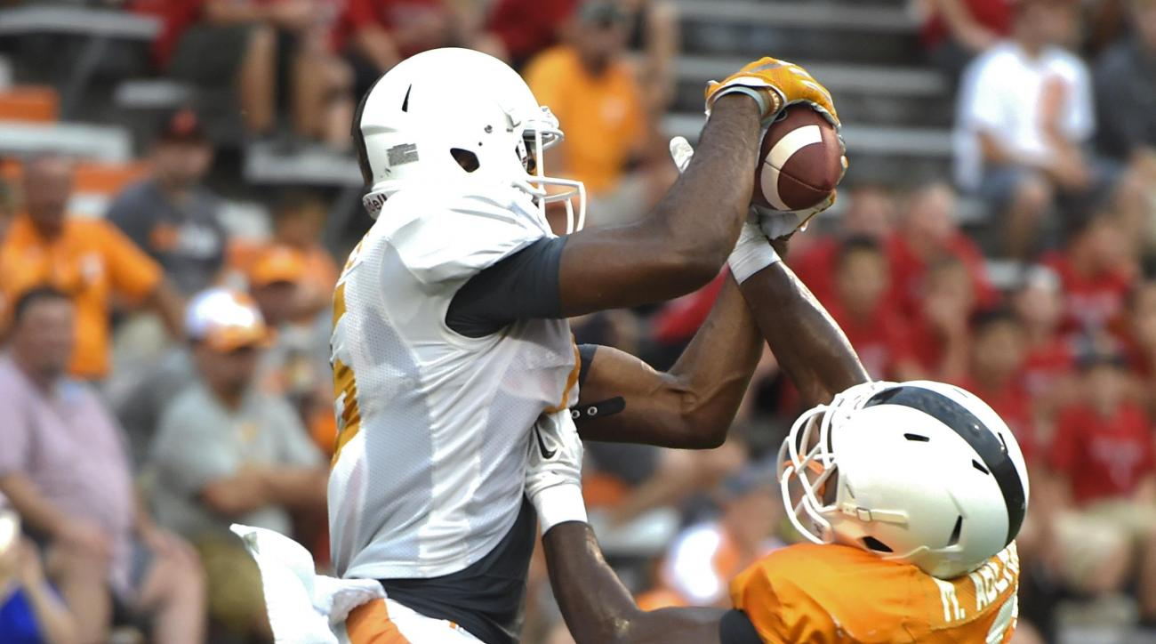 In this Saturday Aug. 15, 2015 photo, Tennessee wide receiver Jauan Jennings, left, makes a catch over defensive back Micah Abernathy during practice in Knoxville, Tenn. Tennessee freshman receiver Jauan Jennings is a former quarterback who just switched