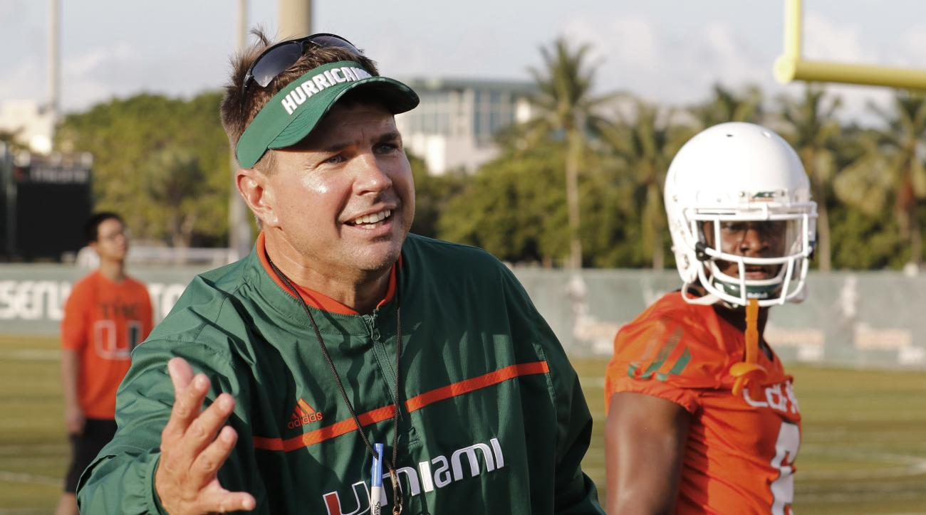 FILE - In this Friday, Aug. 7, 2015 file photo, Miami head coach Al Golden works with his players during an NCAA college football practice in Coral Gables, Fla. The team is not bothered by a national perception that they will struggle this season. Losing