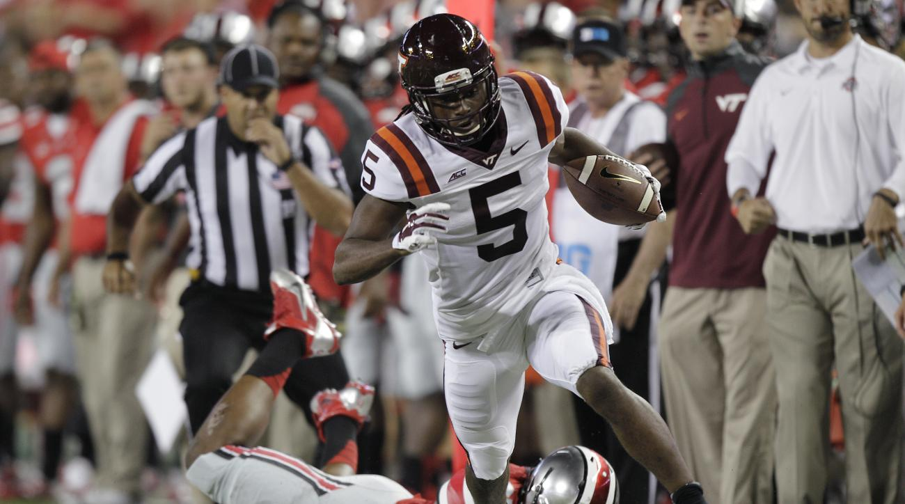 FILE - In this Sept. 6, 2014, file photo, Virginia Tech wide receiver Joshua Stanford gets past a diving Ohio State defender during an NCAA college football game in Columbus, Ohio. College football opens with a long holiday weekend of games, concluding wi