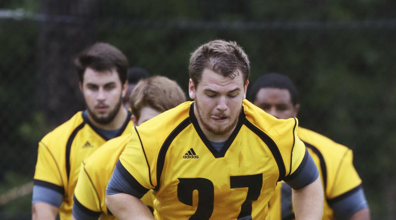FILE - In this Aug. 19, 2014, file photo, Kennesaw State's Joseph Alexander runs drills during an NCAA college football practice in Kennesaw, Ga. One program's starting from scratch. The other is starting over. Kennesaw State will kick off its inaugural s