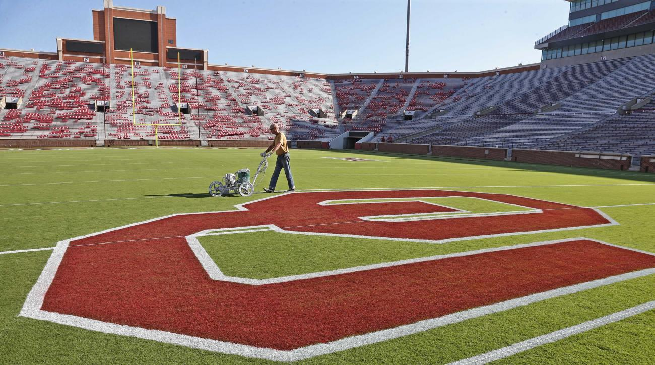 Grounds crew member Mark Moffat paints yard lines on Owen Field at the University of Oklahoma, in Norman, Okla., Thursday, Sept. 3, 2015, in preparation for the first game of the season. Oklahoma faces Akron on Saturday, Sept. 5, 2015. (AP Photo/Sue Ogroc