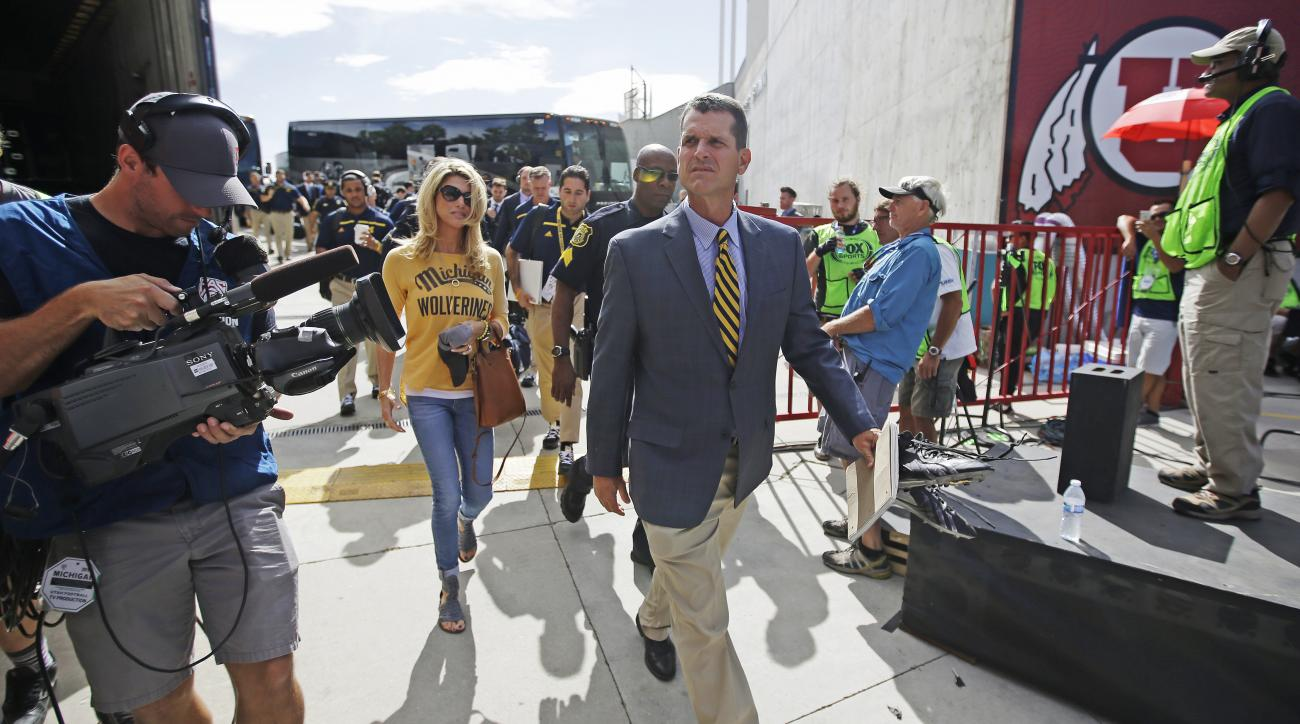 Michigan coach Jim Harbaugh arrives for his team's NCAA college football game against Utah on Thursday, Sept. 3, 2015, in Salt Lake City. (AP Photo/Rick Bowmer)