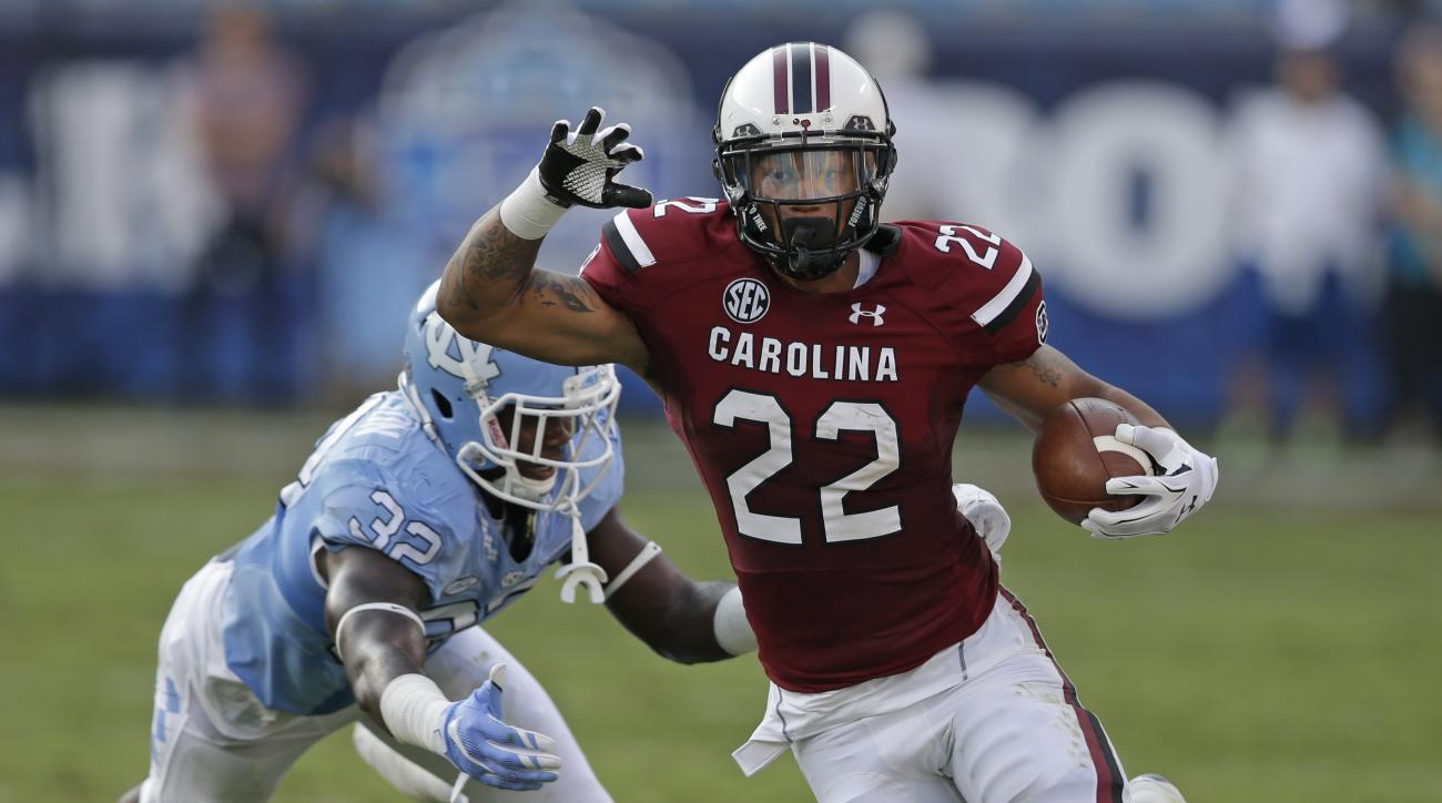 South Carolina's Brandon Wilds (22) runs past North Carolina's Joe Jackson (32) in the first half of an NCAA college football game in Charlotte, N.C., Thursday, Sept. 3, 2015. (AP Photo/Chuck Burton)