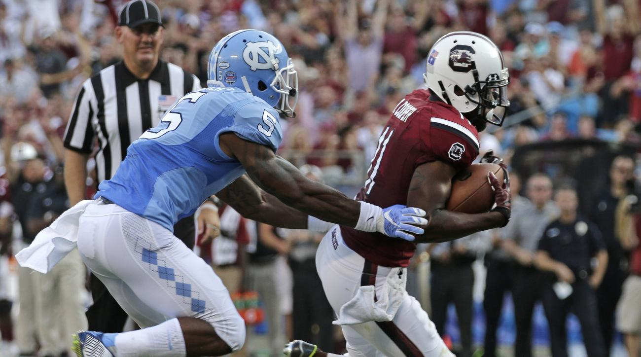 South Carolina's Pharoh Cooper (11) runs past North Carolina's Brian Walker (5) for a touchdown in the first half of an NCAA college football game in Charlotte, N.C., Thursday, Sept. 3, 2015. (AP Photo/Chuck Burton)