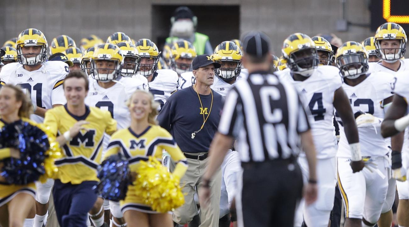 Michigan head coach Jim Harbaugh leads his team on the field before the start of their NCAA college football game against Utah, Thursday, Sept. 3, 2015, in Salt Lake City. (AP Photo/Rick Bowmer)