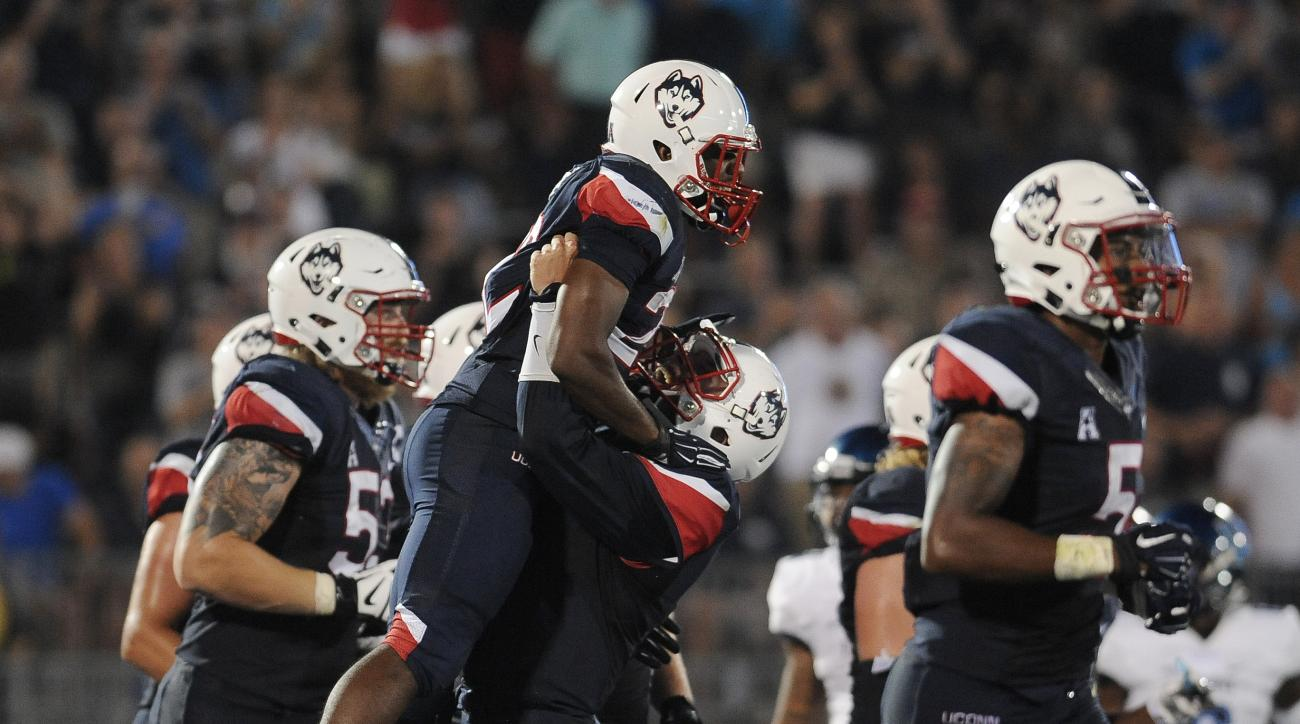 Connecticut running back Arkeel Newsome is lifted into the air by Connecticut quarterback Bryant Shirreffs after Newsome scored a touchdown during the second half of an NCAA college football game at Rentschler Field, Thursday, Sept. 3, 2015, in East Hartf