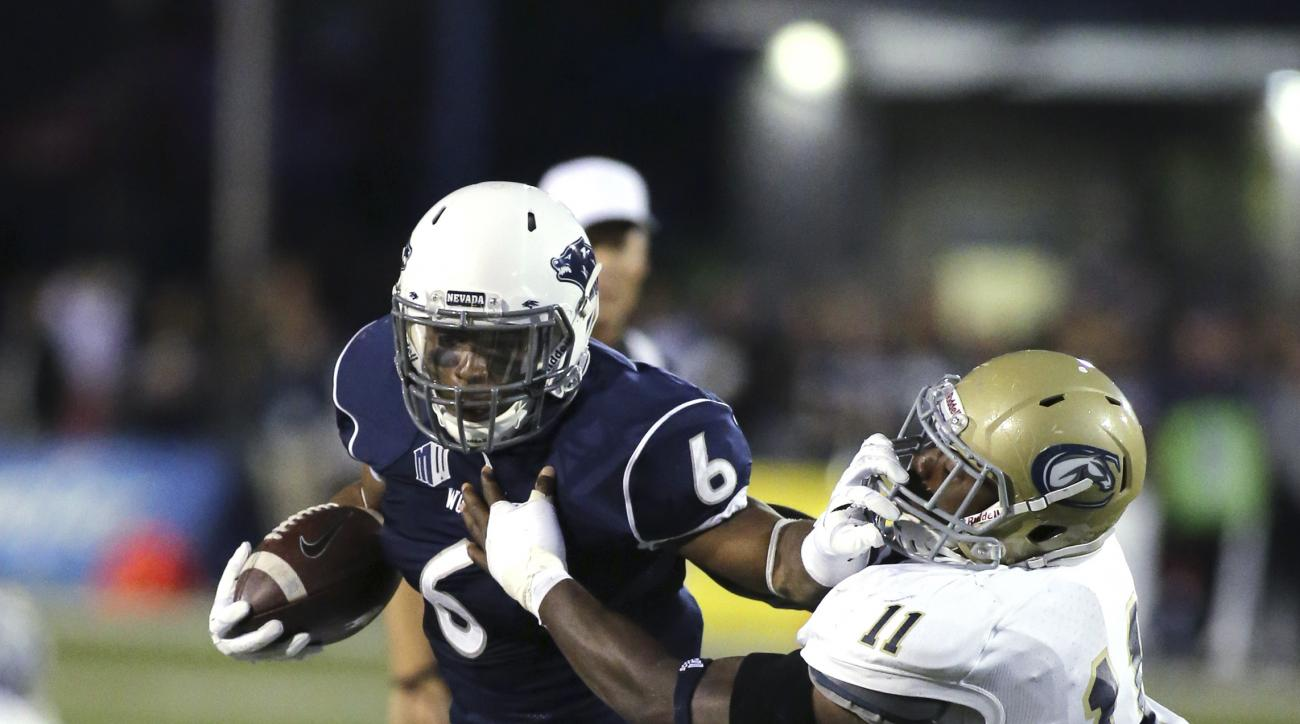 Nevada's Don Jackson (6) runs up the middle against UC Davis' Artice Nelson (11) during the first half of an NCAA college football game in Reno, Nev.. on Thursday, Sept. 3, 2015. (AP Photo/Cathleen Allison)