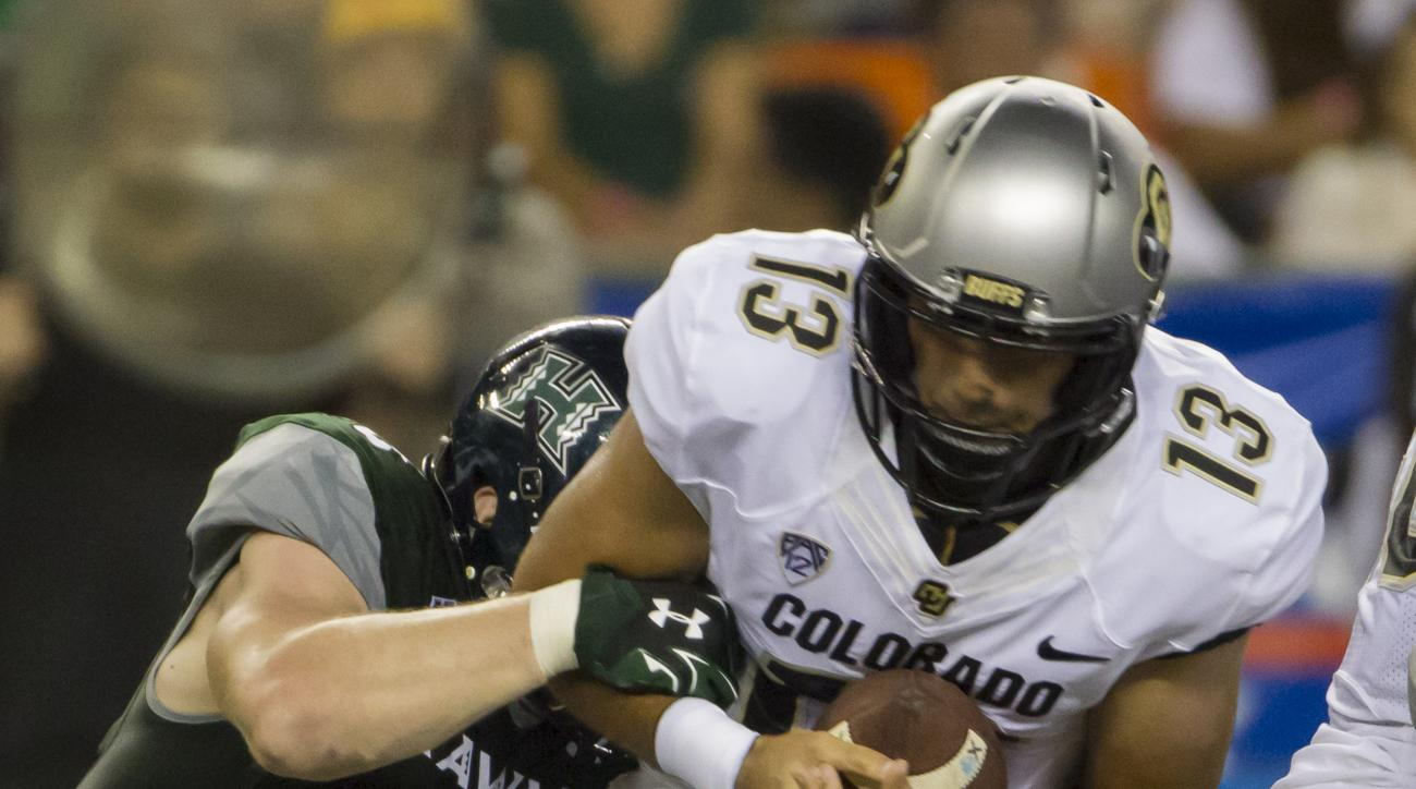 Hawaii defensive lineman Luke Shawley (93) grabs a hold of Colorado quarterback Sefo Liufau (13) and tackles Liufau for a sack in the first quarter of an NCAA college football game, Thursday, Sept. 3, 2015, in Honolulu. (AP Photo/Eugene Tanner)