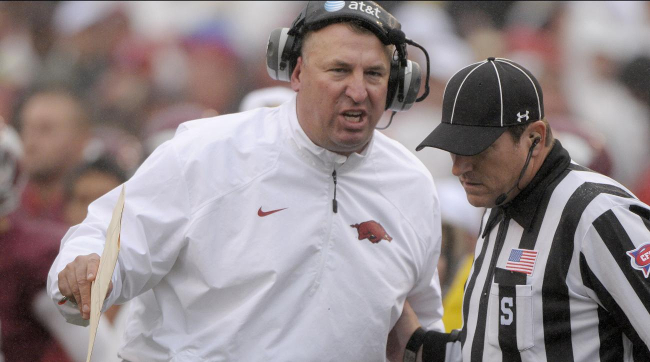 FILE - In this file photo taken Oct. 11, 2014, Arkansas coach Bret Bielema, left, talks to an official during the fourth quarter of an NCAA college football game against Alabama in Fayetteville, Ark. Brandon Allen and Bret Bielema's careers have been link