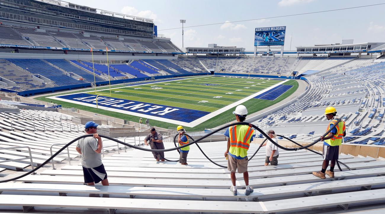 In this Wednesday, Sept. 2, 2015, photo, a crew holds the hose as Rodney Moberly cleans the seats at Commonwealth Stadium in Lexington, Ky. Kentucky players have many reasons to be excited about Saturday night's opener against Louisiana-Lafayette. The big