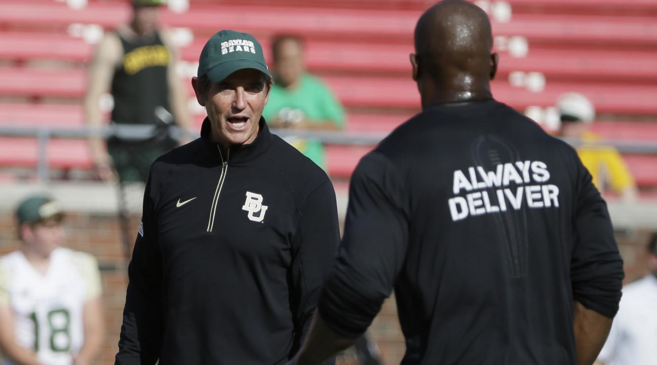Baylor head coach Art Briles, left, walks on the field as his team warms up before an NCAA college football game against SMU, Friday, Sept. 4, 2015, in Dallas. (AP Photo/LM Otero)