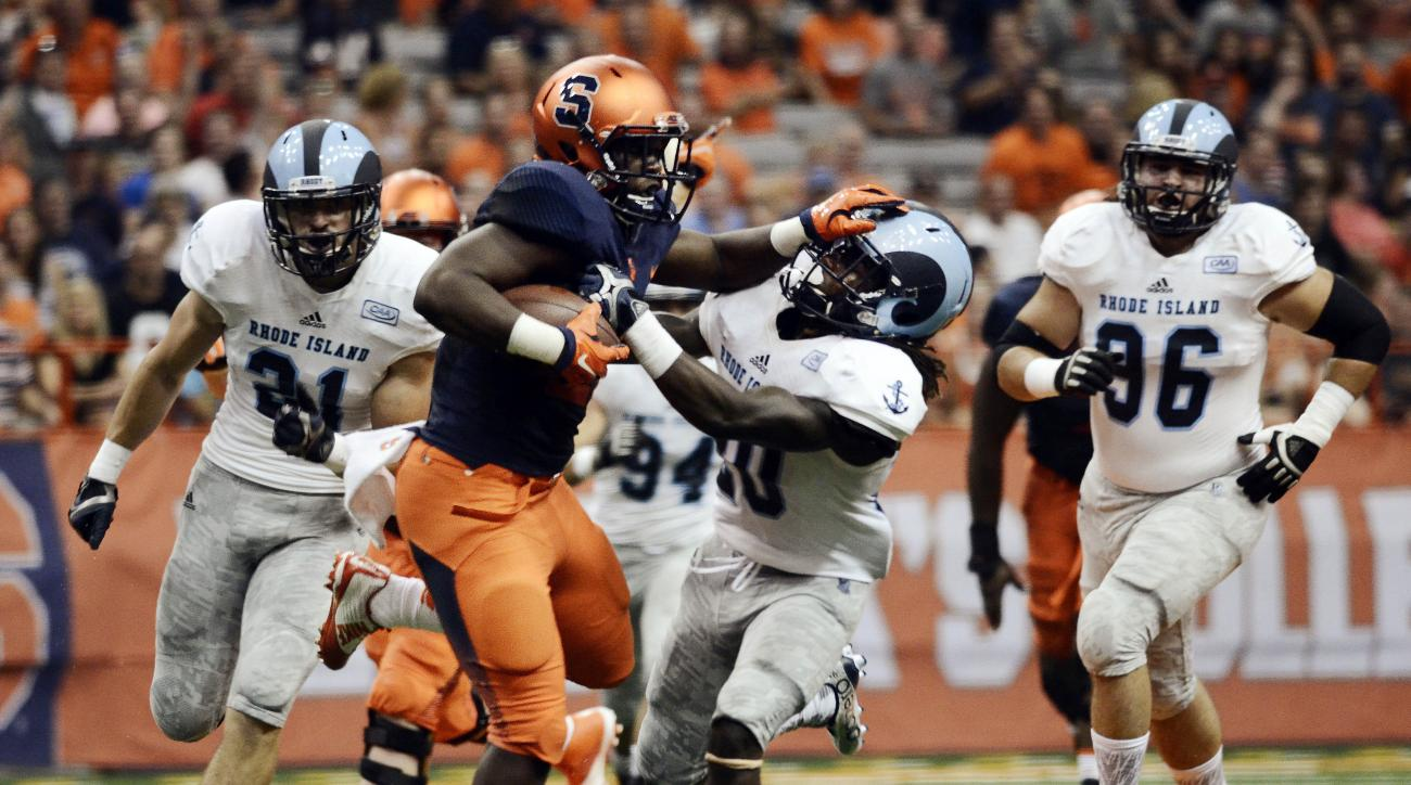 Syracuse's Jordan Fredericks, second from left, fends off Rhode Island's Ahkema Evans during the first half of an NCAA college football game at the Carrier Dome in Syracuse, N.Y., Friday, Sept. 4, 2015, (AP Photo/Heather Ainsworth)